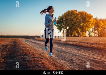 Woman holding bouteille d'eau dans le champ d'automne au coucher du soleil. Concept de vie sain. Sportifs actifs