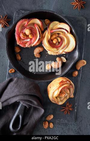 Trois des feuilletés en forme de rose avec des tranches de pomme au four dans une poêle en fonte. Haut lay sur fond sombre avec des draps et serviettes noix caramélisées