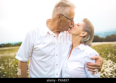Un couple en plein air dans un champ de marguerites Banque D'Images