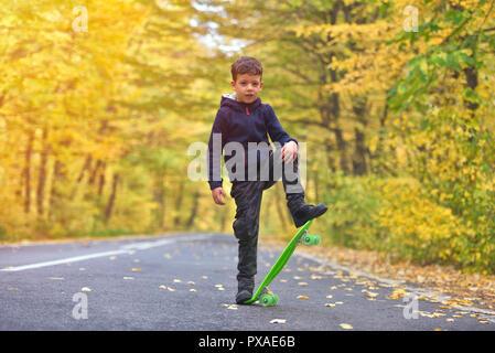 Skateboarder Kid faire skateboard tricks en environnement d'automne Banque D'Images