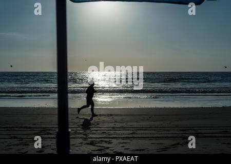 Elle court sur la plage vue depuis le parapluie Banque D'Images