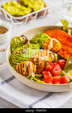 Rainbow bowl végétalien: boulettes de légumes, l'avocat, la patate douce et de la salade. Régime alimentaire à base de plantes concept. Banque D'Images