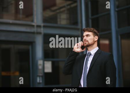 Businessman walking hors du bureau et de conversations au téléphone cellulaire. Homme d'affaires de vêtements formels la marche à l'extérieur à l'aide de téléphone mobile. Banque D'Images