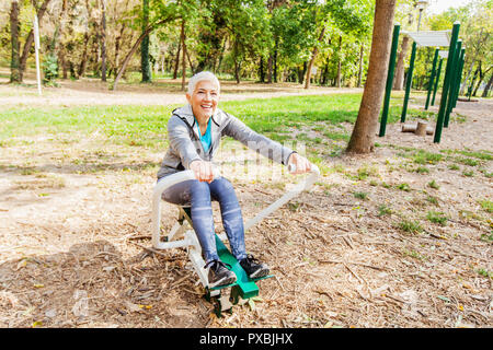 Vieille Femme dans l'exercice de sports de vêtements de plein air au parc de remise en forme avec rameur, bonne hygiène de vie personnes âgées.