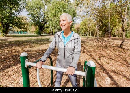 Vieille Femme dans l'exercice de sports de vêtements de plein air au parc de remise en forme, les modes de vie des personnes mûres.