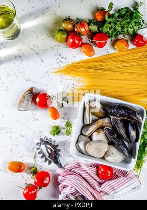 Ingrédients pour la cuisson des spaghettis aux fruits de mer. Musselsa coquilles, palourdes, vongole, les tomates et le vin blanc. Banque D'Images