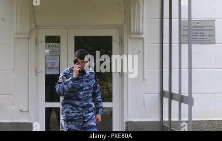 Kerch, la Russie. 22 octobre, 2018. KERCH, Crimée, RUSSIE - 22 octobre 2018: un officier de police par l'école de formation professionnelle polytechnique de Kertch. Le 17 octobre 2018, un jeune de 18 ans de l'ordre ont ouvert le feu sur les autres élèves et enseignants et a procédé à une explosion avant de se suicider; 21 personnes ont été tuées dans l'attaque, environ 50 ont été blessés. Valery Matytsin/crédit: TASS ITAR-TASS News Agency/Alamy Live News Banque D'Images