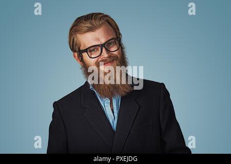 Portrait of handsome businessman hipster barbu portant des lunettes en souriant heureux isolé sur fond bleu. La face positive d'expression, l'émotion humaine, b Banque D'Images