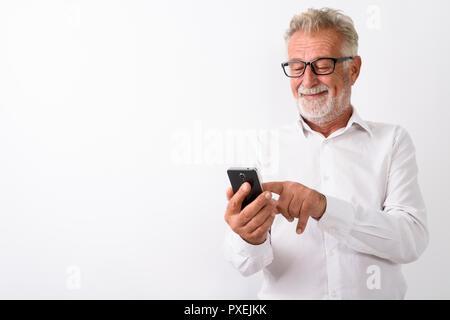 Studio shot of happy senior man smiling barbu lors de l'utilisation de mobi Banque D'Images