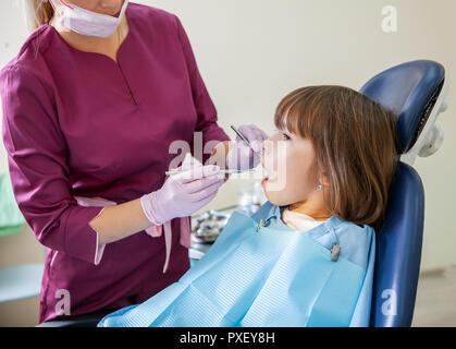 Femme dentiste en cabinet dentaire traite avec les dents du patient pour enfants