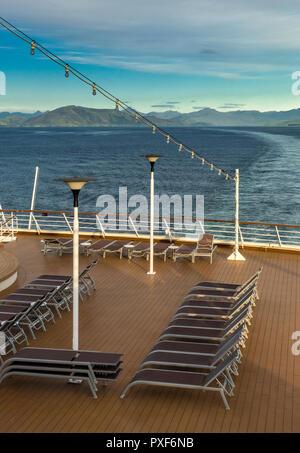 Chaises longues marron vide, à l'arrière sur le pont Lido d'un navire de croisière en fin d'après-midi. L'entrée Dixon, le passage de l'Intérieur, de la Colombie-Britannique, Canada. Banque D'Images