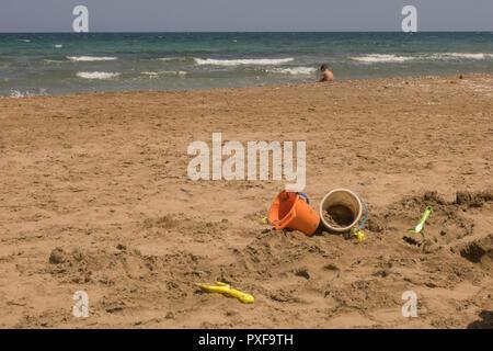 Jouer des seaux et kid au bord de la mer sur le sable Banque D'Images