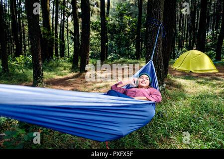 Happy hiker Woman talking on cellphone in hamac sur la forêt Banque D'Images