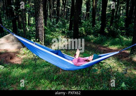 Belle asiatique traveler woman with smartphone en hamac sur la forêt Banque D'Images