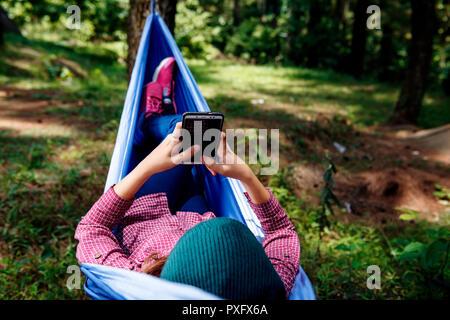Young Asian woman using mobile phone randonneur tout en vous relaxant dans un hamac à forest Banque D'Images