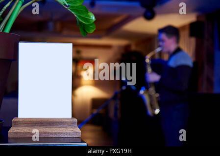 Étiquette de la Maquette un cadre vide menu dans un restaurant bar, support pour brochures avec des feuilles de papier blanc contre un arrière-plan flou d'un saxophoniste p Banque D'Images