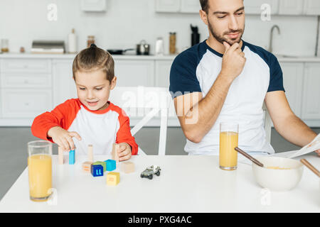 Man reading newspaper tout en jouant avec son fils dans la cuisine à table cubes Banque D'Images