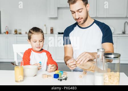 Père et fils en jouant avec des blocs en bois et un jouet avion après le petit-déjeuner dans la cuisine Banque D'Images