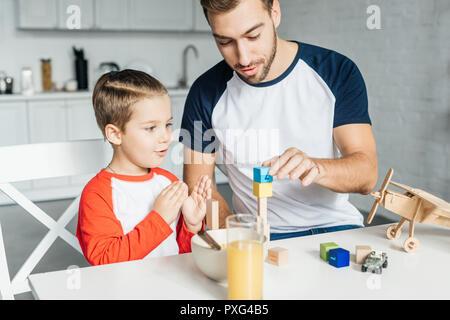 Père et fils en jouant avec des blocs de bois après le petit-déjeuner dans la cuisine Banque D'Images