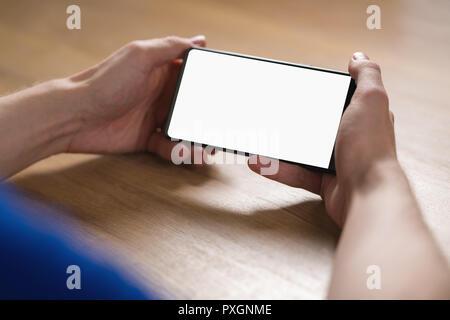 Jeune homme hands holding Smartphone avec écran blanc en mode paysage  Banque D Images ae5526c0a88b