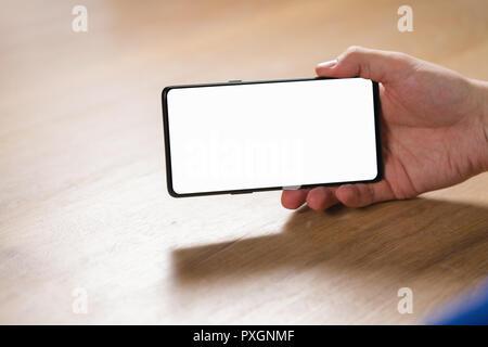 Moins du cadre isolé smartphone  Jeune homme hand holding Smartphone avec  écran blanc en mode paysage Banque D Images 9e808aabf110