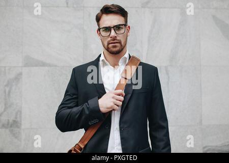 Businessman standing contre un mur carrelé portant un sac de bureau. Jeune homme portant des lunettes et portant un sac de bureau standing outdoors. Banque D'Images