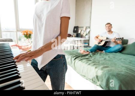 Vue partielle de l'homme jouant de la guitare acoustique sur le lit tout en jouant au piano électronique amie accueil Banque D'Images