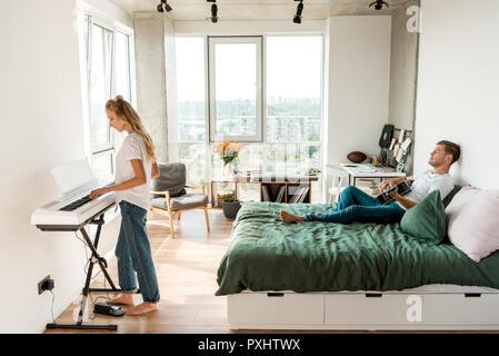 Vue latérale d'homme jouant de la guitare acoustique sur le lit tout en jouant au piano électronique amie accueil Banque D'Images