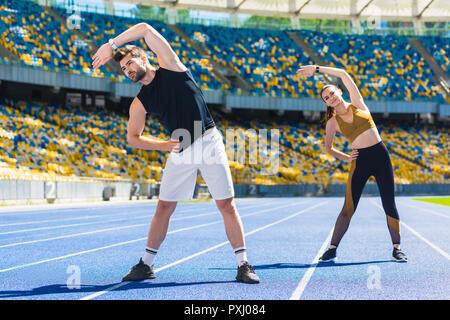 Young sportive woman side bend avant l'entraînement sur une piste de course au stade de sport Banque D'Images