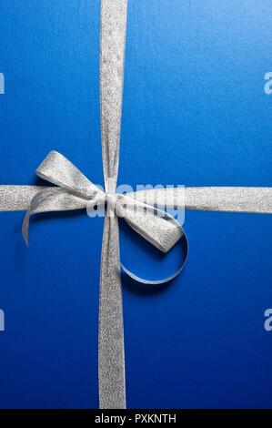 Un cadeau enveloppé de papier bleu et de ruban argent Banque D'Images