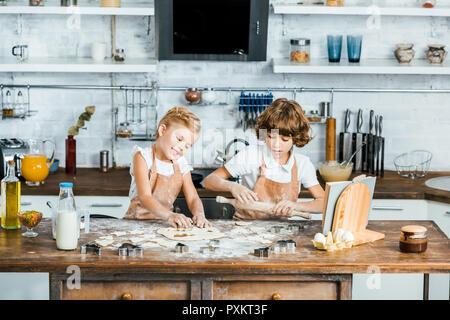 Tabliers mignon enfants heureux dans la préparation de délicieux cookies ensemble Banque D'Images