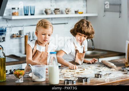 Adorables enfants dans les aires de préparation de la pâte à biscuits savoureux Banque D'Images
