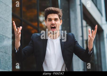 Portrait d'homme en colère, furieux d'avoir dépression au travail, hurlant de colère, la gestion du stress, problèmes de détresse mentale, la perte de sang-froid, la réaction en cas d'échec Banque D'Images