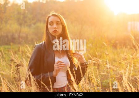 Belle jeune femme triste marche à l'herbe sèche, heure du coucher de soleil.