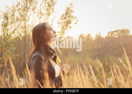 Belle jeune femme triste marche à l'herbe sèche, vue de profil