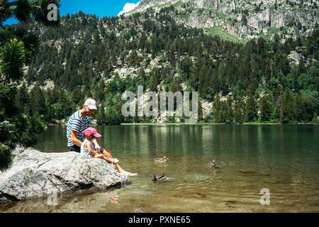 L'Espagne, le père et la fille assise sur un rocher à un lac de montagne, l'alimentation des canards Banque D'Images