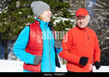 Mature couple sportif en vêtements d'hiver en jogging dans la forêt le matin Banque D'Images