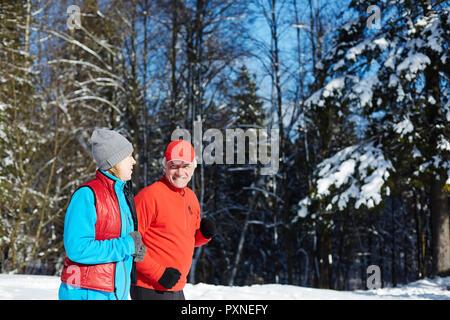 Les conjoints dans les vêtements d'avoir parler en faisant du jogging dans la forêt ou le parc d'hiver Banque D'Images