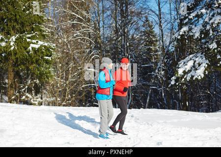 Senior Actif en forêt en hiver neige le matin Banque D'Images