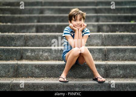 Portrait de petite fille assise détendue dans les escaliers