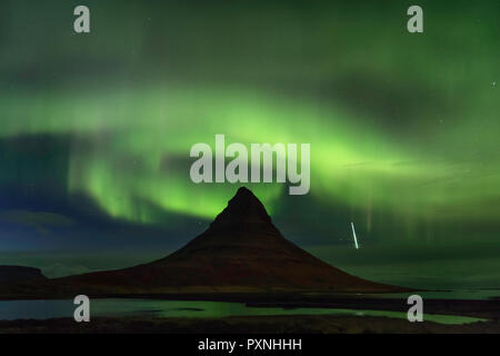 Grundarfjörður, Islande - Les aurores boréales spirale autour de haut de la sommet du Mont Kirkjufell comme une étoile filante passe à travers l'atmosphère. Banque D'Images