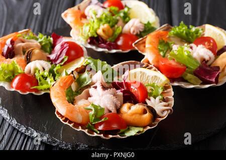 Délicieuse salade de fruits de mer cuits, crevettes, moules, poulpes bébé de calmars et de pétoncles avec légumes dans les coquillages close-up sur la table horizontale. Banque D'Images