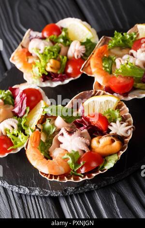 Salade de fruits de mer gastronomique de crevettes, poulpe bébé, moules, calmars et de pétoncles en coquilles de mer gros plan sur la table verticale. Banque D'Images