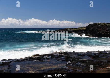 Rivage sur Grande Île d'Hawaï près de South Point. Bleu profond de l'océan Pacifique, les vagues se brisant sur le littoral. Petite cuvette en premier plan. Banque D'Images