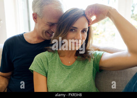 Portrait of happy young couple sitting on sofa at home