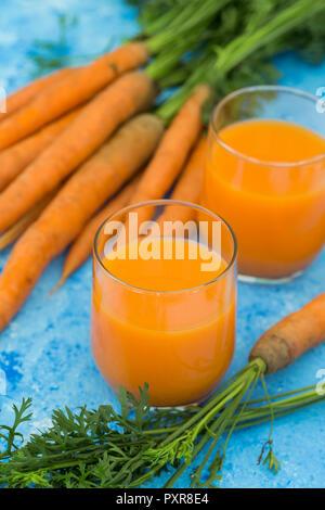 Deux verres de jus de carottes fraîches et les carottes sur la masse bleu clair Banque D'Images
