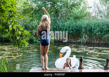 Deux filles dans un étang avec piscine gonflable jouet en forme de cygne Banque D'Images