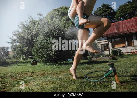 Frère et sœur jouant avec tuyau de jardin en jardin