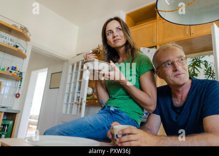 Confiant mature couple at home looking sideways