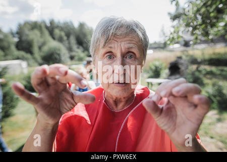 Portrait of senior woman gesturing dans le jardin